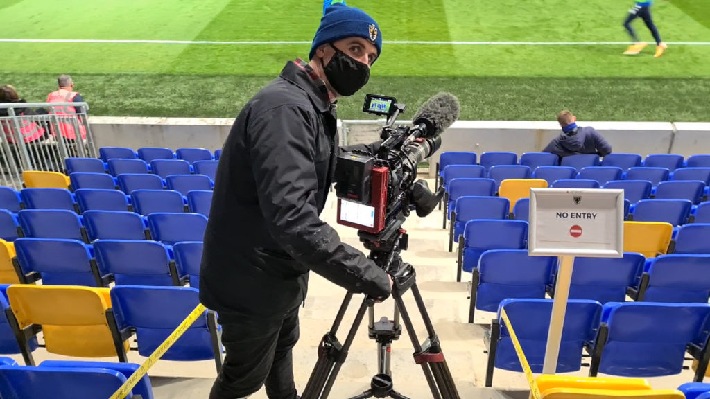 A person opereating a camera at a football stadium